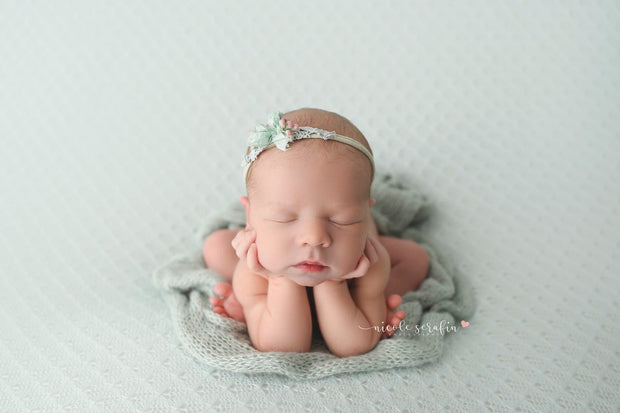 newborn girl in froggy pose with light blue/green mohair wrap under her