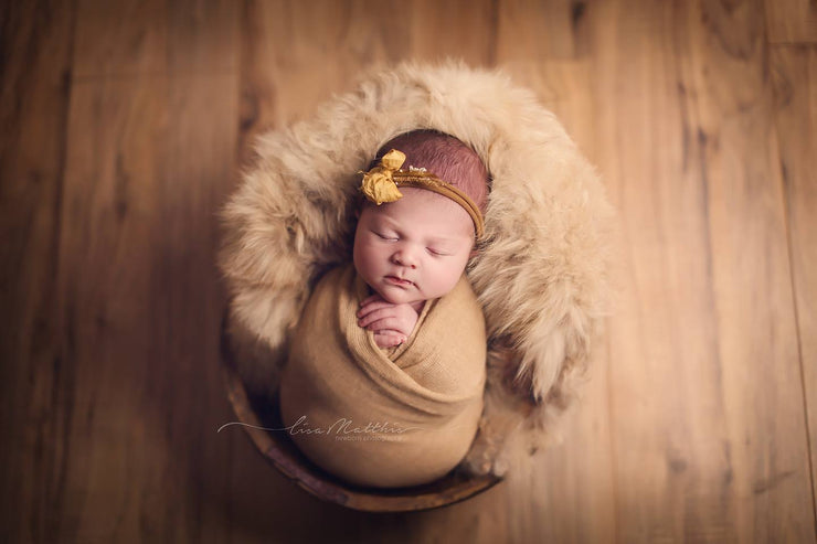 rustic wooden bowl and newborn in yellow wrap and fur with headband