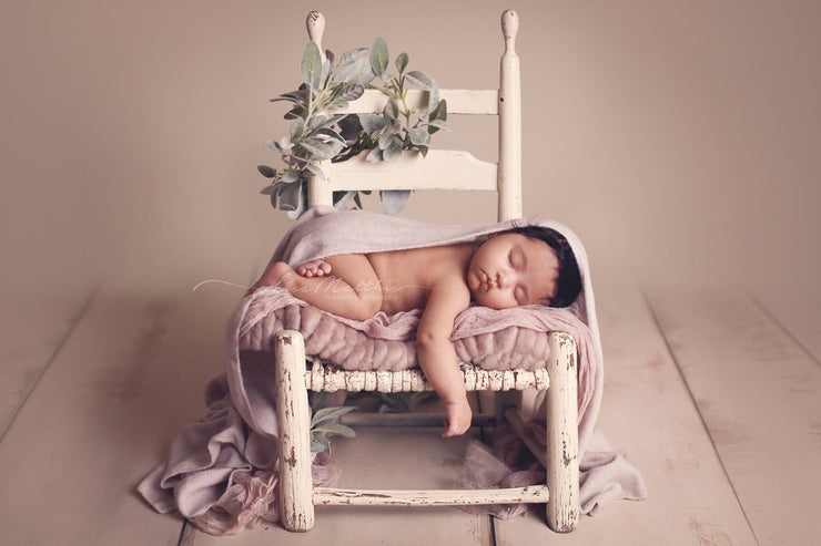 light purple newborn baby girl fuzzy swaddling wrap. baby girl on white chair