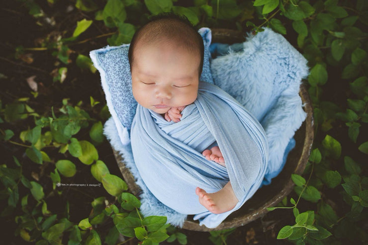 newborn baby boy swaddled in blue wrap, rabbit pelt and pillow by custom photo props