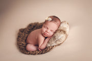 newborn baby girl with head on brown mini fur pillow