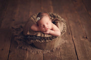 newborn baby girl with brown chunky layering blanket photography props