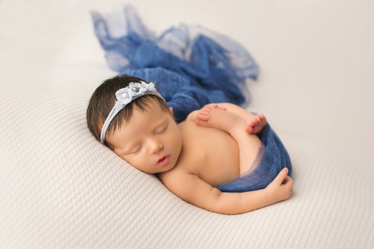 newborn girl swaddled in silk layering fabric with matching blue headband