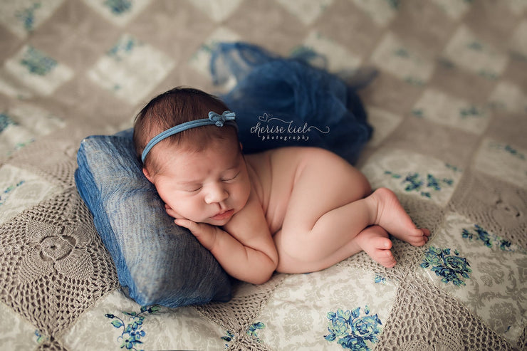 newborn girl with blue headband, and pillow on quilt photography props