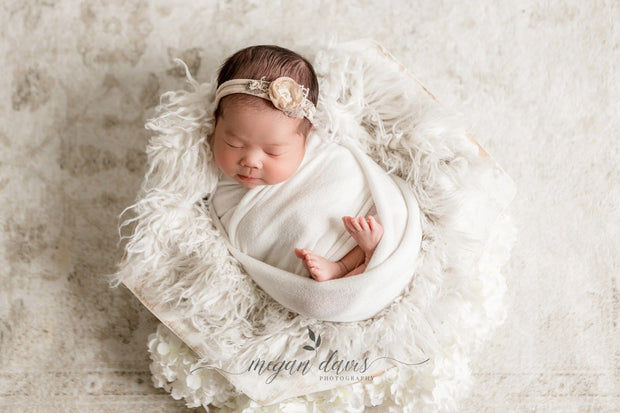 newborn baby girl on faux flokati fur in white wooden bowl faukati