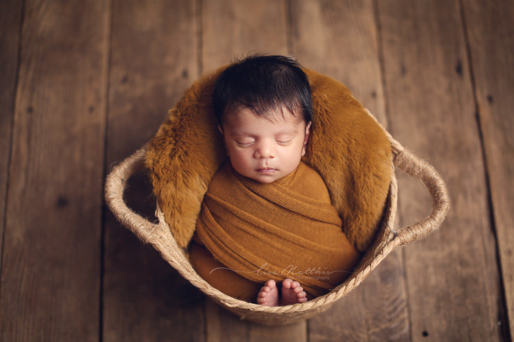 newborn baby in copper colored rabbit pelt and swaddling wrap