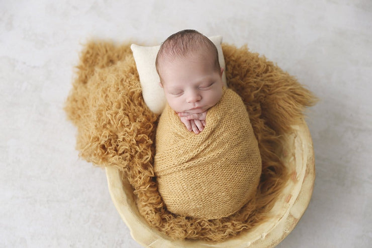 mustard yellow faux flokati newborn fur photography prop with boy swaddled in yellow wrap