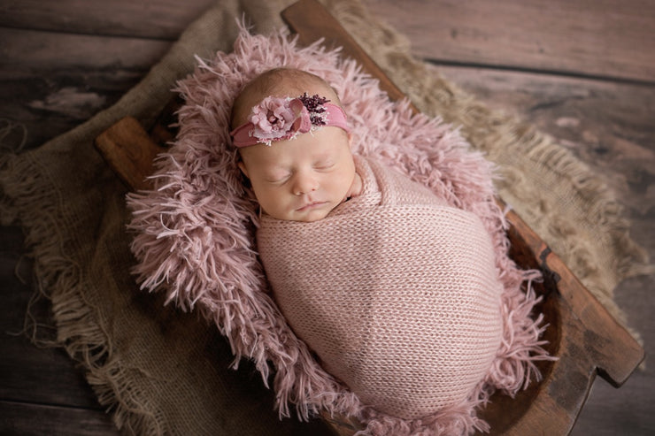 pink faux fur with newborn baby girl in trench bowl and pink swaddling wrap
