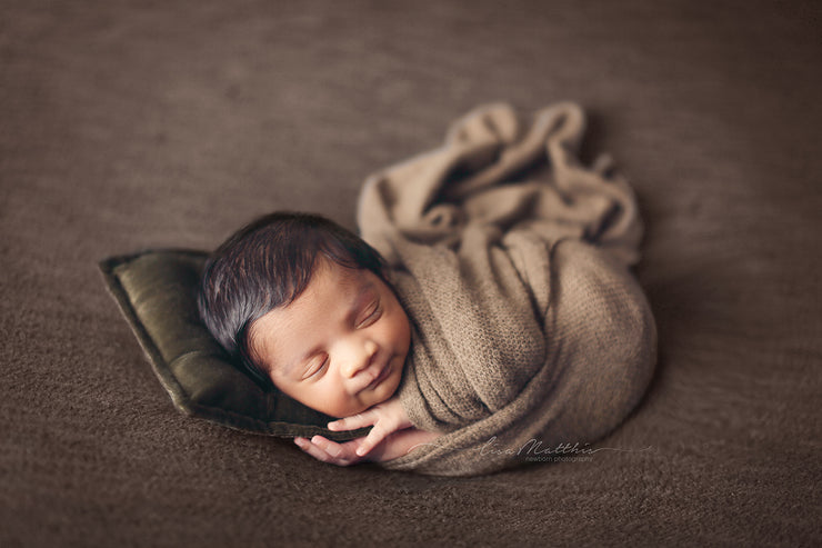 light brown fuzzy newborn baby swaddled in wrap and with small pillow