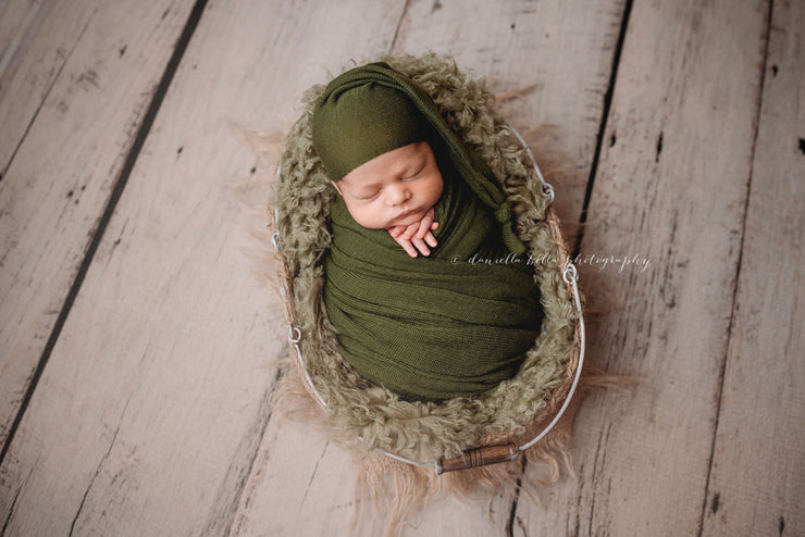newborn baby boy in green sleepy hat and swaddle and green wool fur photo prop.