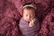 newborn baby girl swaddled in potato sack pose with fuzzy purple stretch swaddling blanket wrap