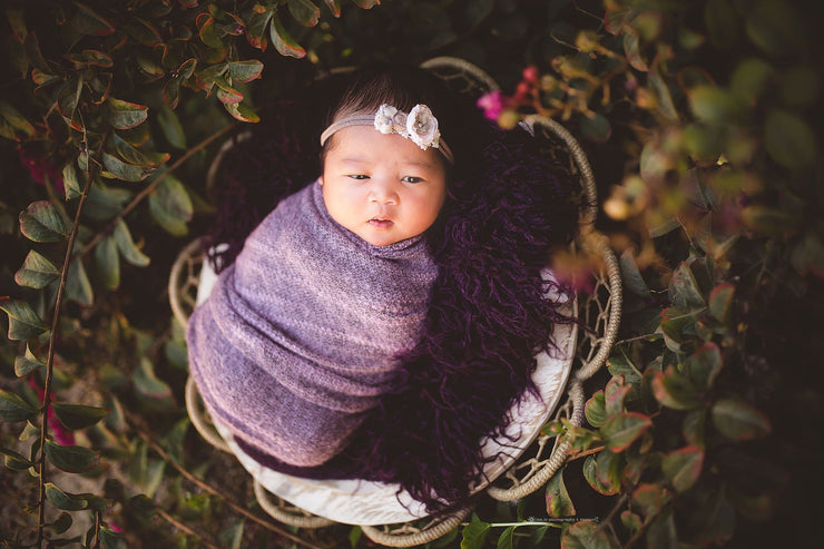 darker skin newborn baby with purple stretch swaddling wrap photo prop