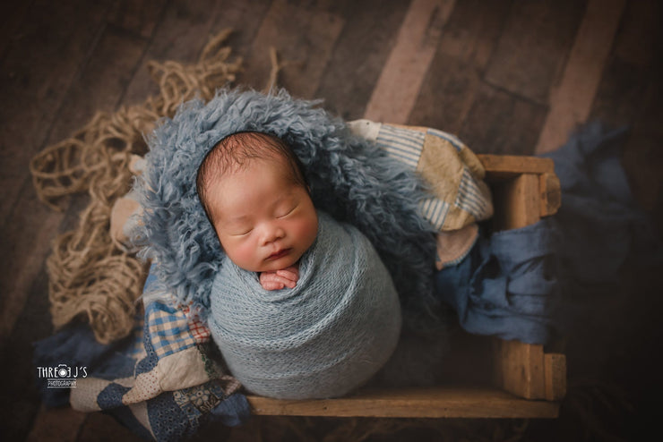 wavy blue faux fur fabric under baby boy for newborn pictures. Swaddled in custom photo props mohair wrap
