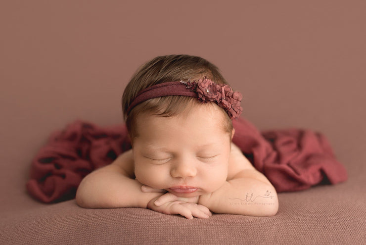 newborn girl photos with deep pink swaddling wrap and matching headband