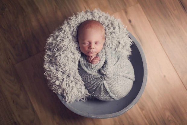 baby sleeping on soft light gray faux fur and wrapped in a gray mohair wrap photography prop