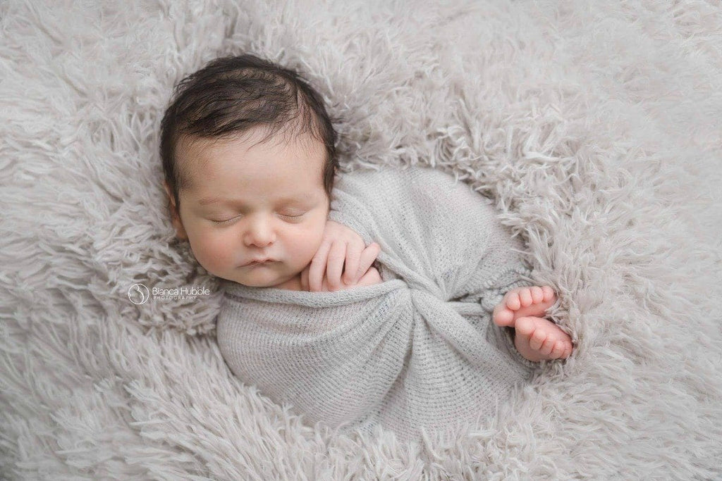 baby on light gray fur and wrapped in a gray mohair wrap