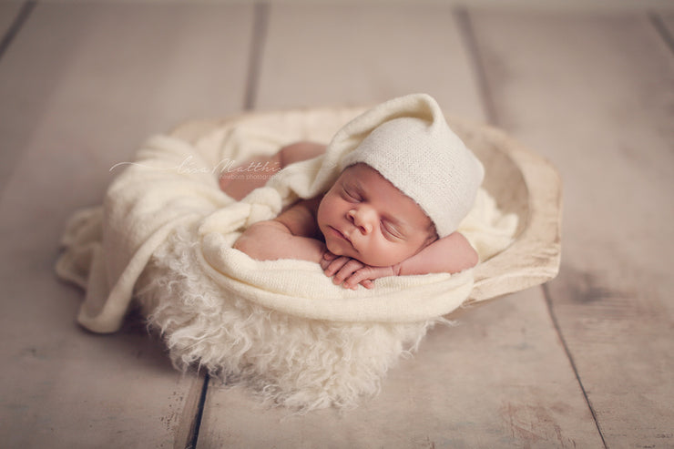 newborn baby boy in all white and ivory. flokati wool faux fur, fuzzy sleepy hat and wrap. newborn baby photo props
