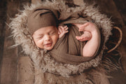 newborn baby boy swaddled in brown swaddling wrap by Custom Photo Props