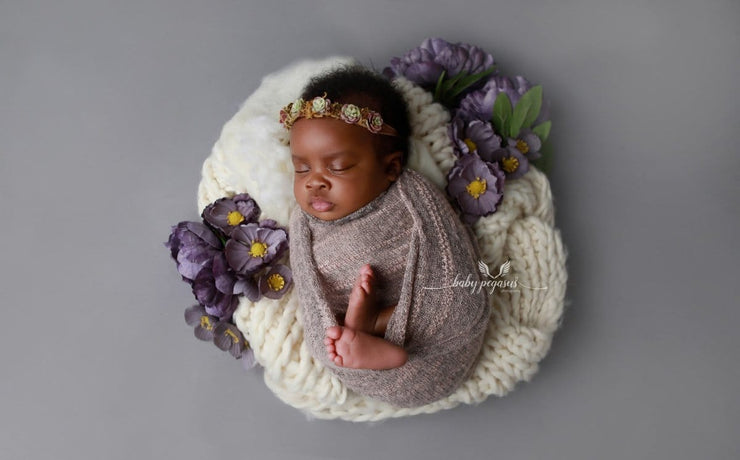newborn baby girl swaddled in fuzzy pink stretch wrap photo prop by custom photo props