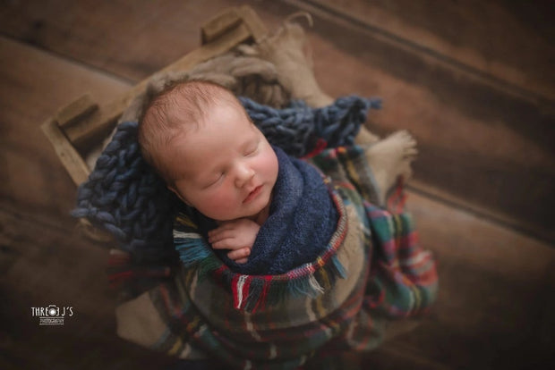 newborn baby boy with dark blue chunky knit blanket newborn photos