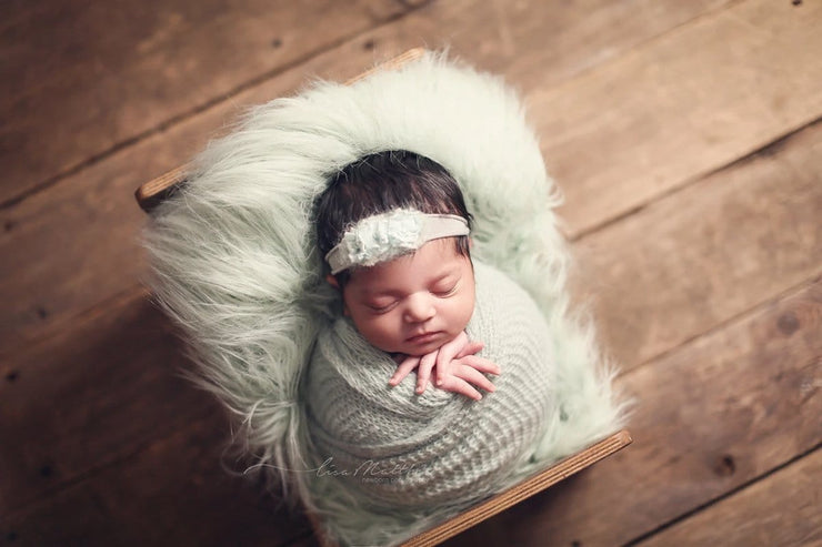 newborn baby girl swaddled in green mohair wrap for baby's first photos