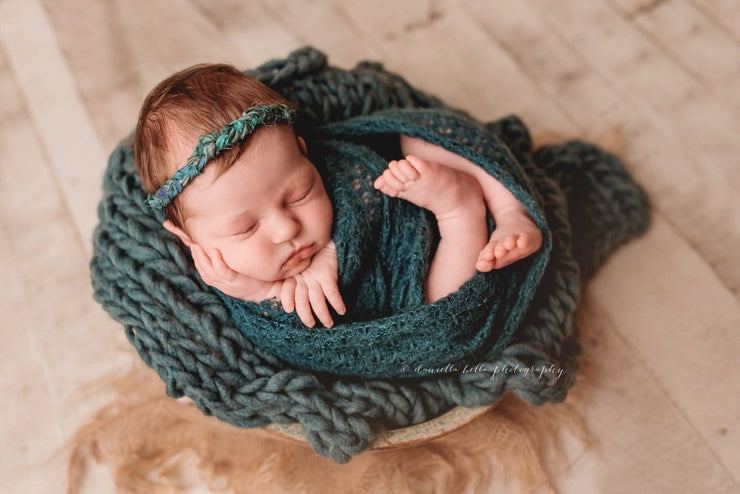 hand knit, chunky yarn, blue green layering blanket with baby girl in bowl