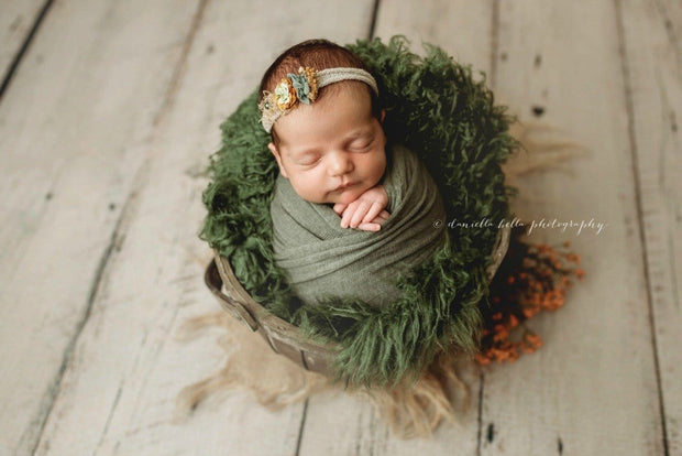 dark green faux fur and matching swaddling wrap and headband on newborn girl