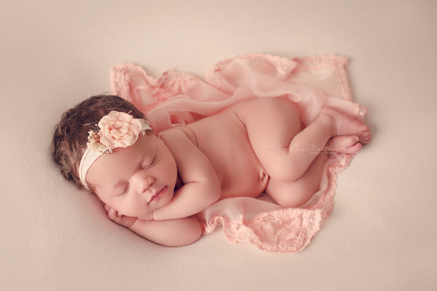 newborn baby girl with peach headband and peach lace layering fabric photo prop studio set