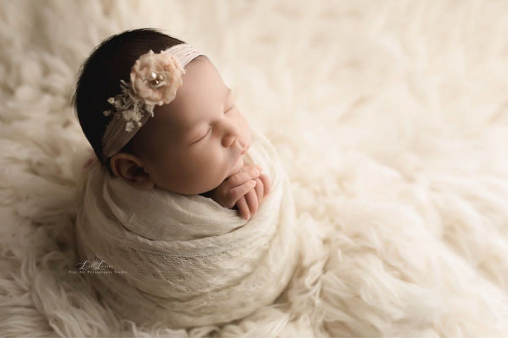 newborn baby girl swaddled in textured fabric with headband