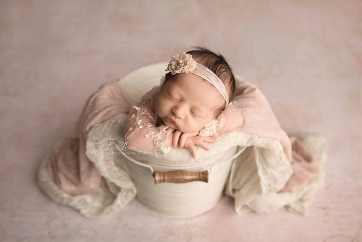 newborn baby girl sleeping in bucket with textured fabric flowing over sides