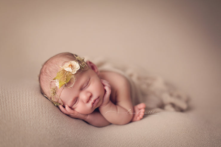 newborn baby girl posed with hemp and flower halo