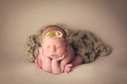 newborn baby girl headband with flower petal and hemp with moss. baby girl in froggy pose.