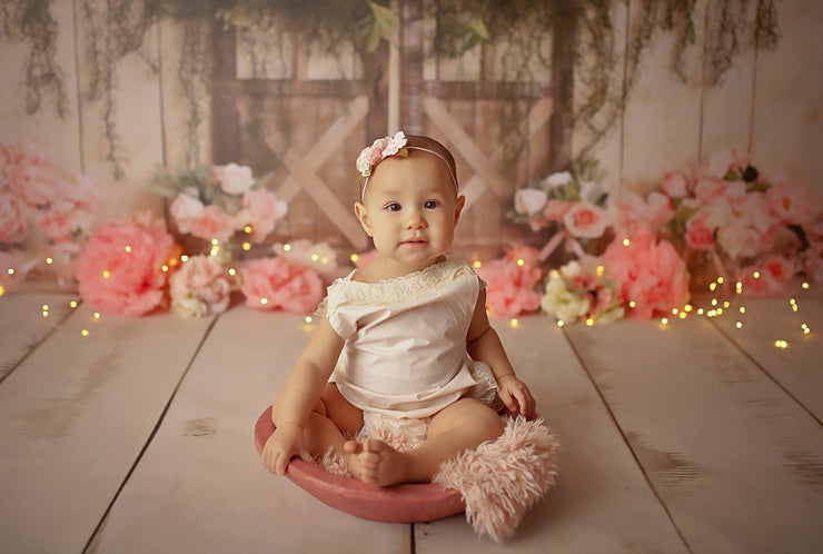 little girl sitting in round wood bowl photography prop with small fur