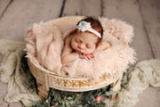 large peach newborn baby fur inside large wood posing prop