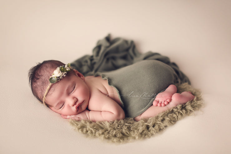 newborn baby girl in ivory swaddle wrap and green faux flokati fur photography props
