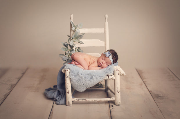 newborn baby girl with blue flower headband on chair and green foliage