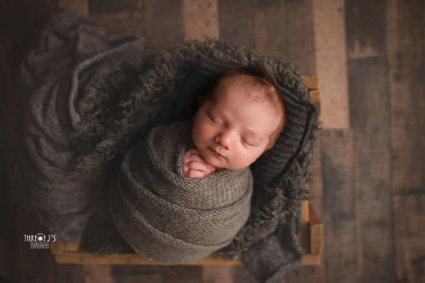dark gray faux flokati fur with newborn boy wrapped in dark gray mohair swaddle photo prop