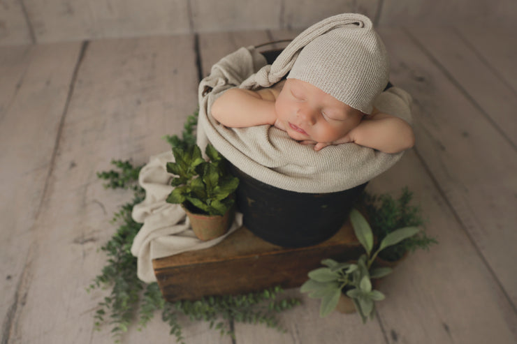 beige newborn sleepy hat with posing fabric in bucket and with foliage