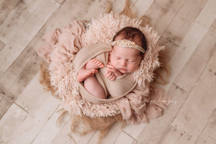 newborn baby girl in bowl with soft peach fur fabric