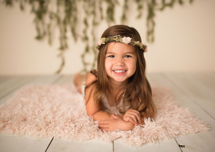 little girl laying on soft peach faux fur fabric during photos