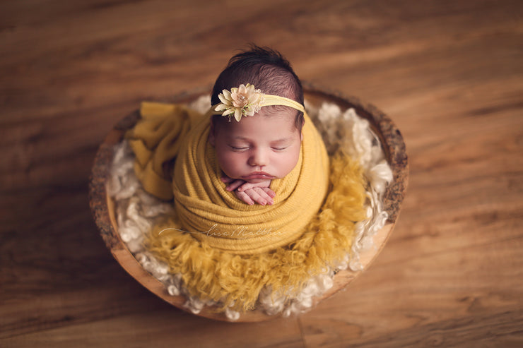 newborn girl with yellow headband, faux flokati fur and fuzzy swaddling wrap