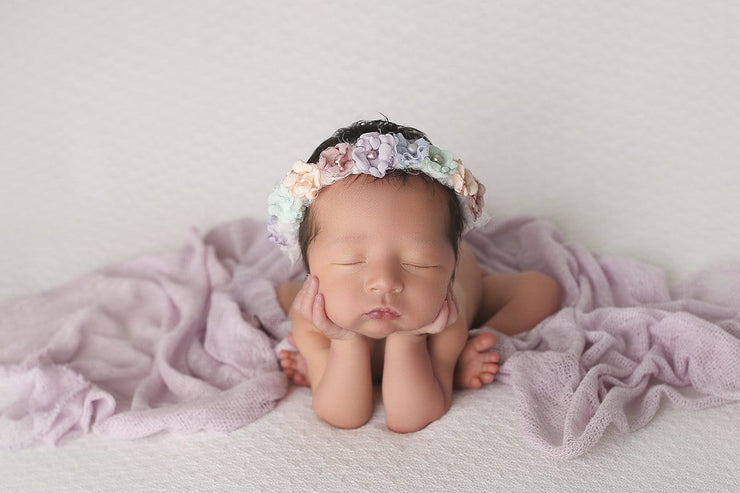 light purple baby wrap and newborn girl wearing matching halo in rainbow colors