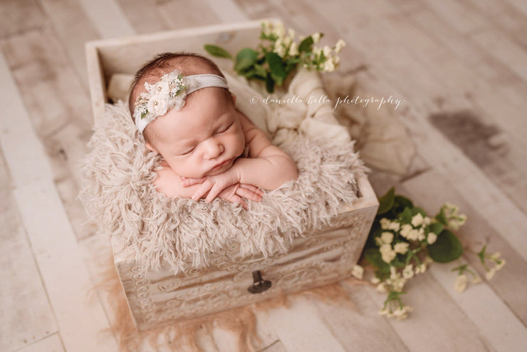 newborn baby girl in white craved drawer with fur and headband photo props