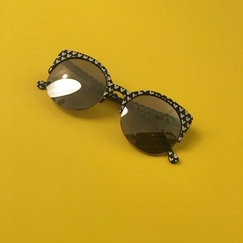 8a0eb5f454a9 I get a ton of questions on my sunglasses! They are black with an almost cat -eye style, with little white Mickey heads along the frame, ...