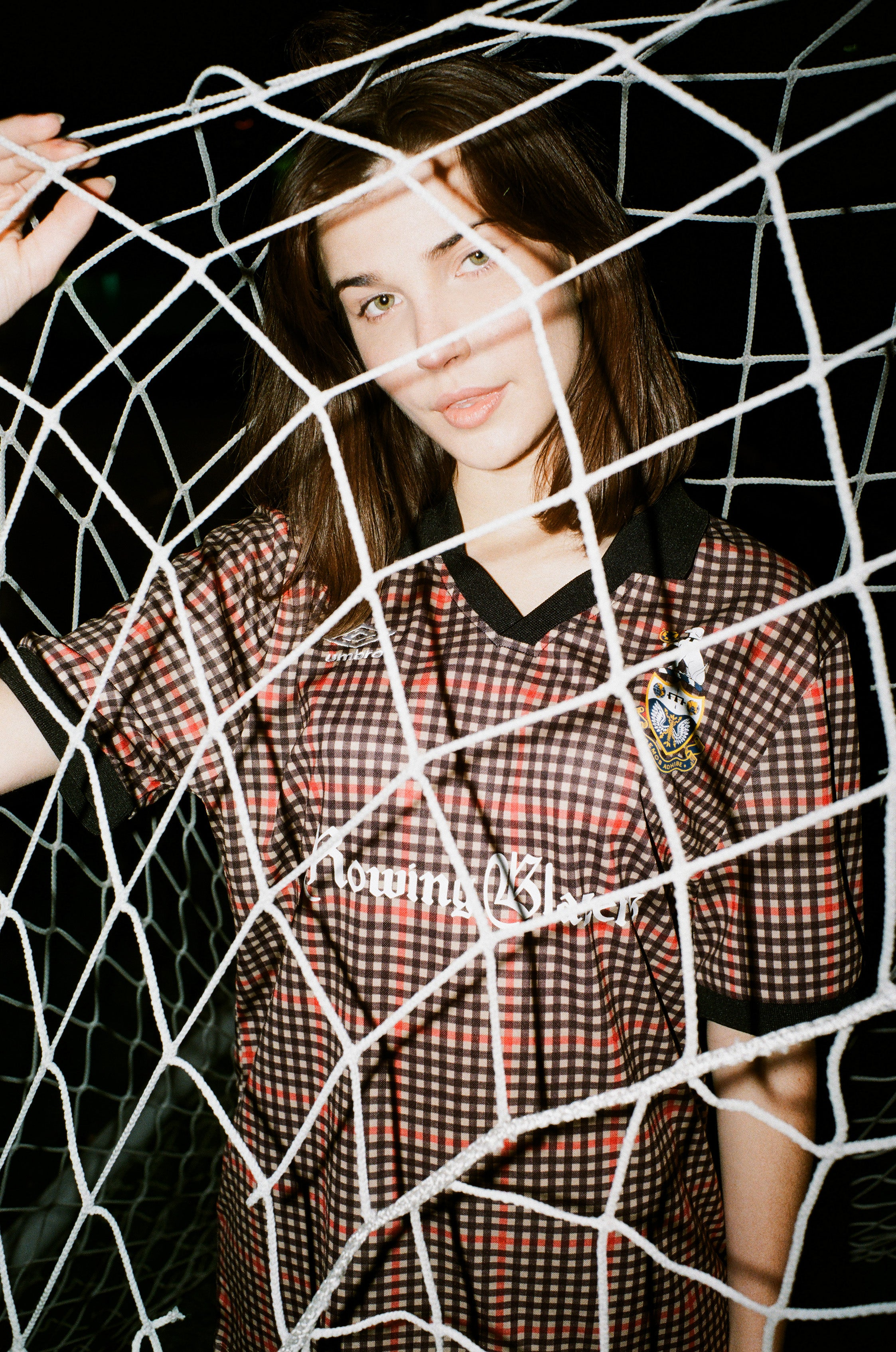 Female model wearing the Rowing Blazers X Umbro Gun Club Check Soccer Jersey standing behind a soccer net