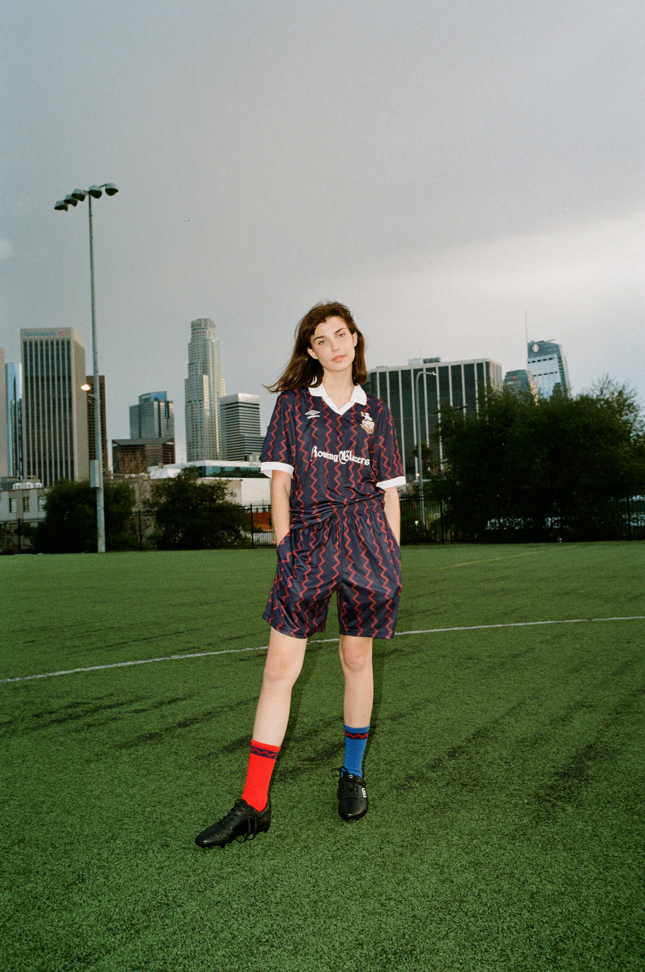 Female model wearing the Rowing Blazers X Umbro Red and Navy Zig-Zag Soccer Jersey and the Soccer Shorts