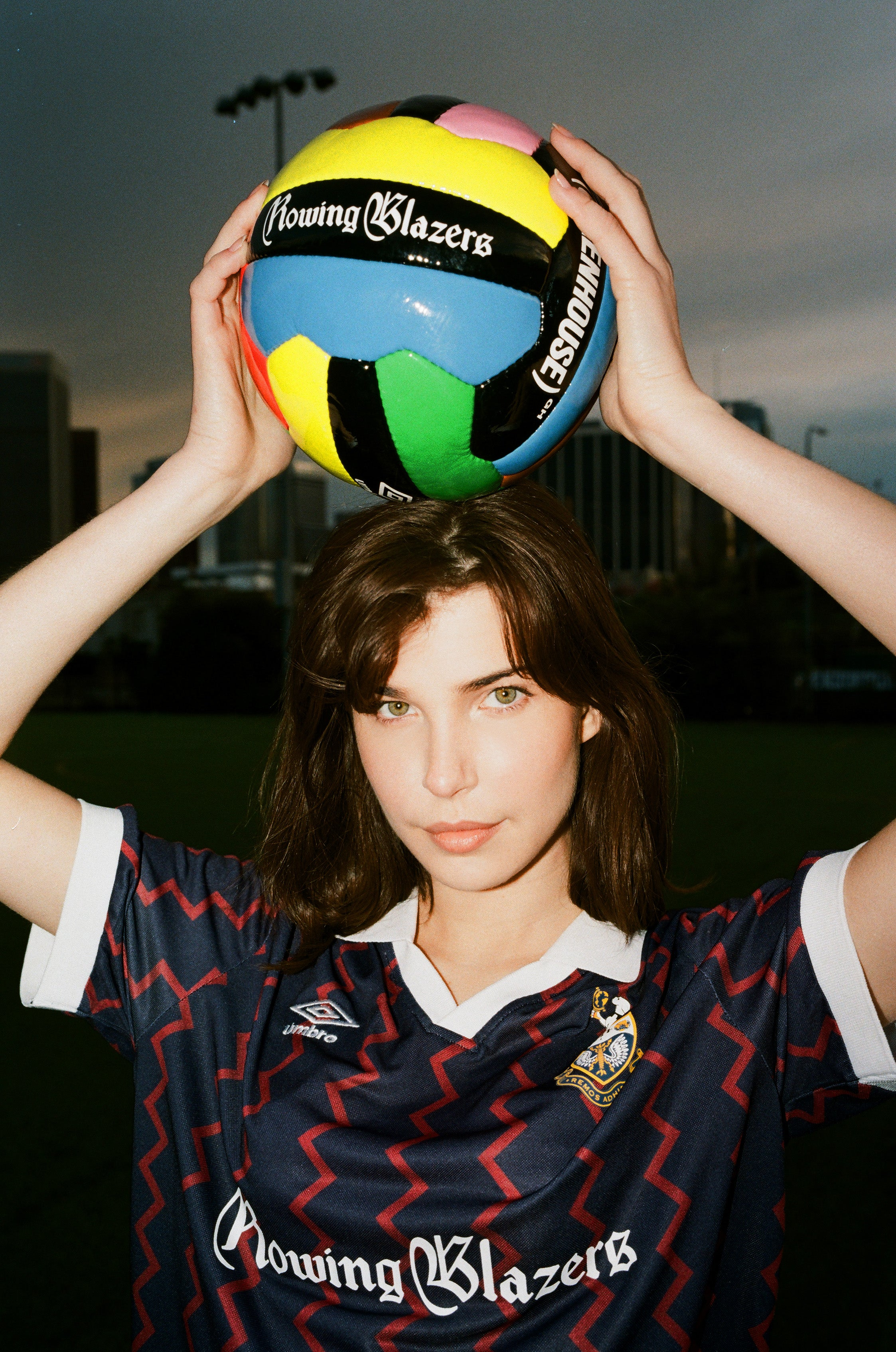 Female model wearing the Rowing Blazers X Umbro Red and Navy Zig-Zag Soccer Jersey holding the Rowing Blazers X Umbro Soccer Ball above her head