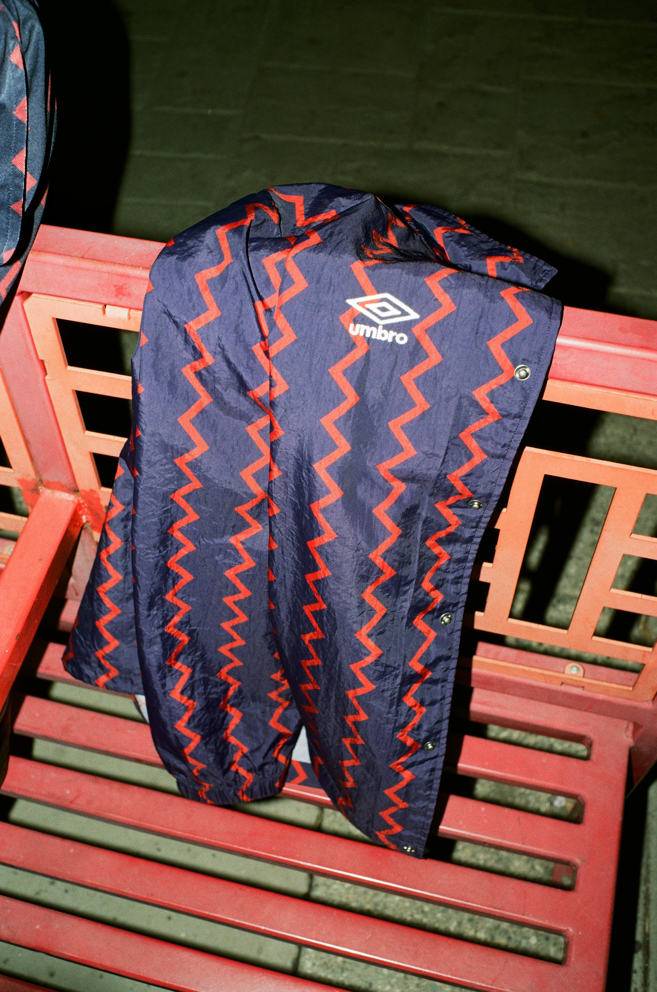 Rowing Blazers X Umbro Red and Navy Zig-Zag Coach's Jacket hanging over a chair