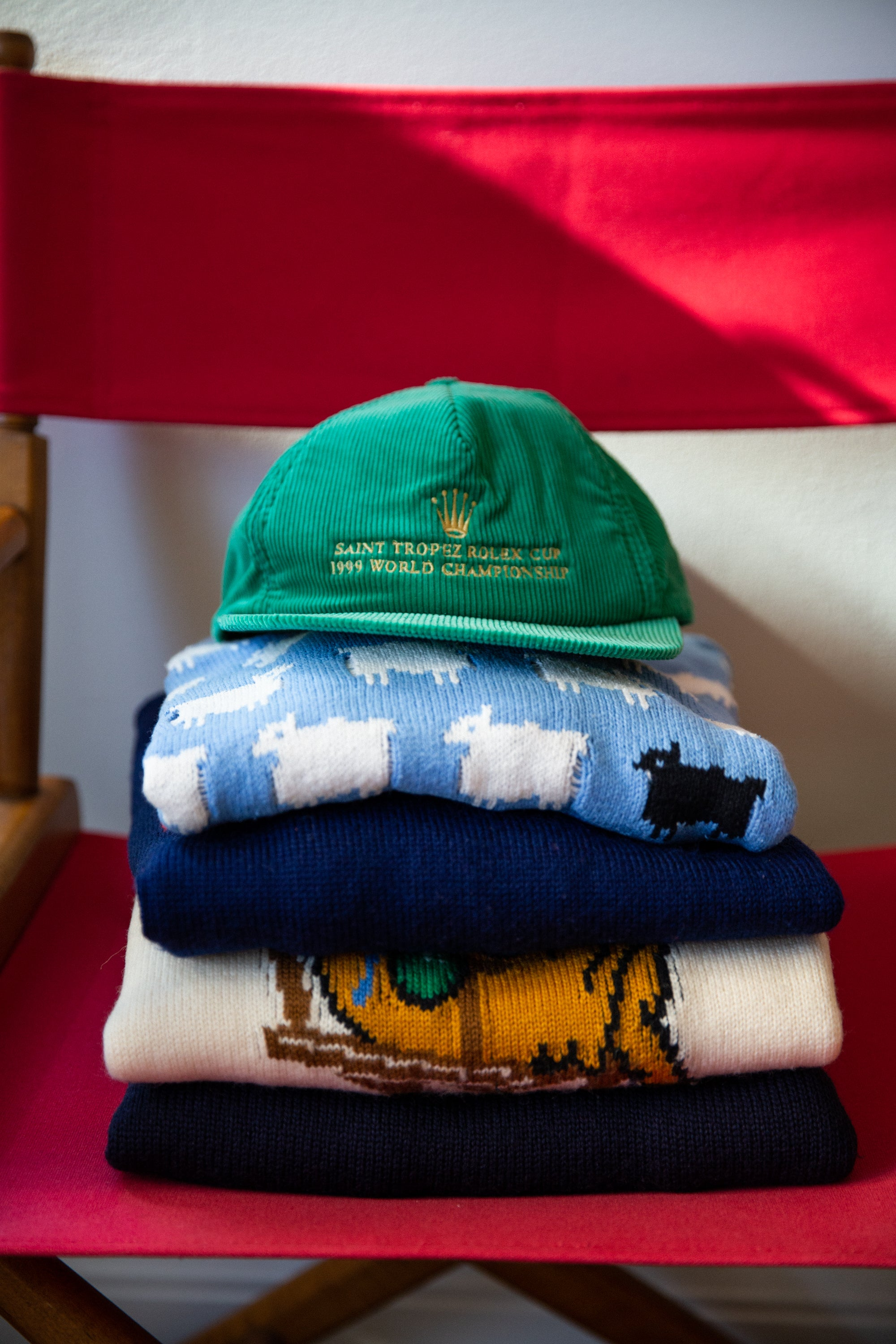 Close-up of a hat on top of various sweaters