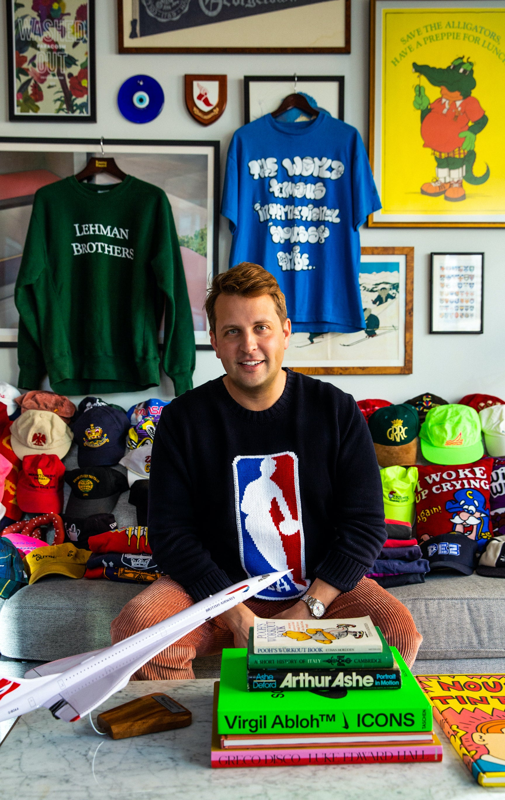 Jack Carlson wearing the NBA sweater in navy sitting on a couch surrounded by different hats